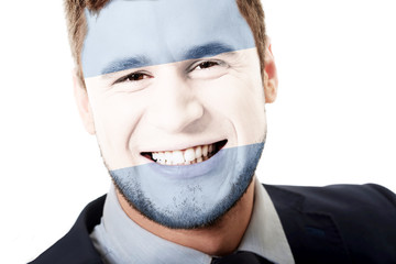 Happy man with Argentina flag on face.