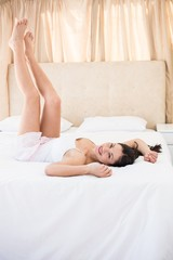 Pretty brunette laughing on bed