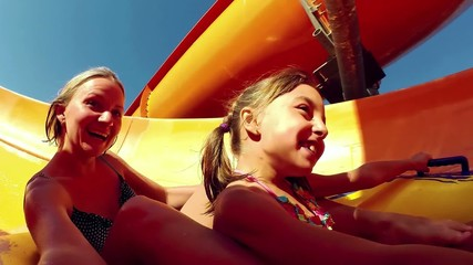 Happy woman with her daughter sliding down the waterslide in a w