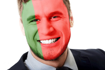 Happy man with Portugal flag on face.