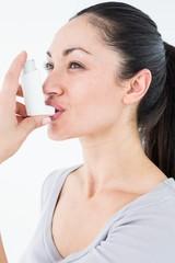 Asthmatic pretty brunette using inhaler