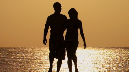 Couple in silhouette embracing on beach at dusk