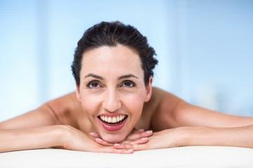 Smiling brunette relaxing on massage table