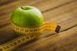 Leinwanddruck Bild - Green apple with measuring tape