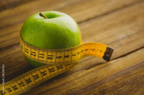 Leinwanddruck Bild Green apple with measuring tape