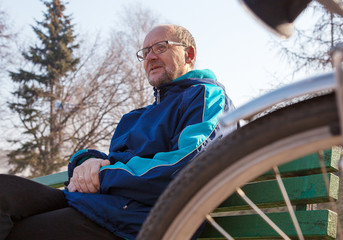 eldely man sitting on a bench near his bicycle in a city park
