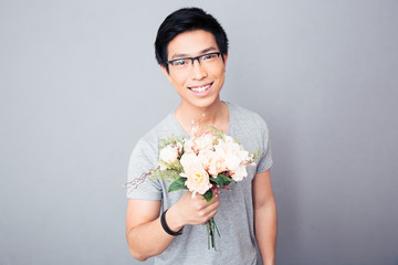 Smiling asian man holding flowers