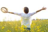 Beautiful young woman enjoying summer in a field.
