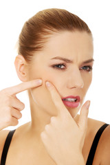 Woman squeezing a pimple.