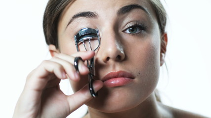 young woman curling eyelashes