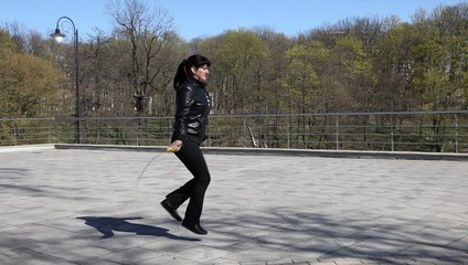young beautiful woman jumping rope and runs out of the frame