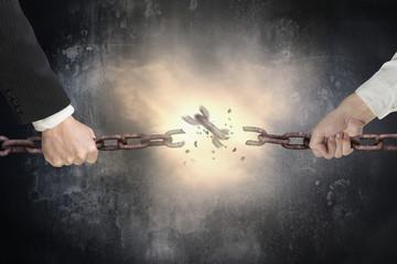 Businessman pulling rusty iron chains broken with dark concrete