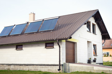 Vacuum solar water heating system on a house roof.