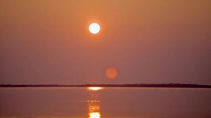 T/L WS Sun rising over water horizon / Merit Island, Florida, USA