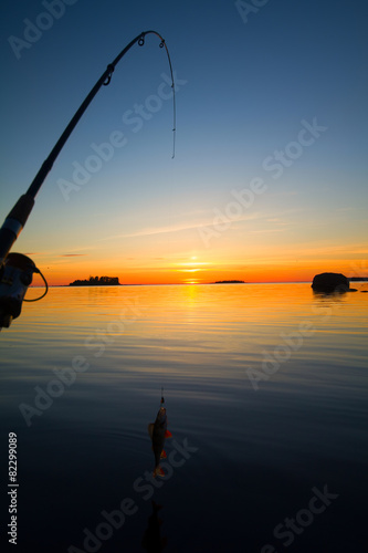 Plexiglas Vissen Sunset river perch fishing with the boat and a rod