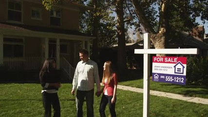 "WS Young couple shaking hands with real estate agent and hugging in front of  suburban house with ""For Sale"" sign on lawn, Provo, Utah, USA"
