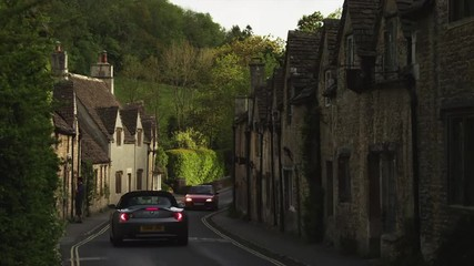 WS Two cars on village road / Castle Combe, Cotswolds, Wiltshire, UK