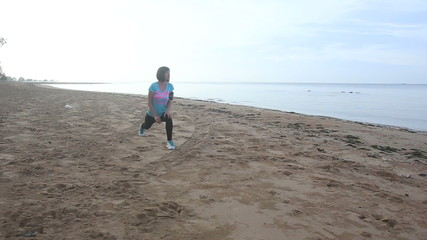 young european girl starts doing morning exercises on beach
