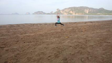 young european girl does gymnastics on beach at dawn