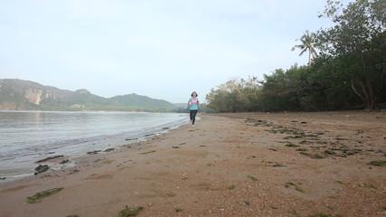 young european girl runs along beach at sunrise