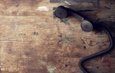Retro telephone reciever on wooden table