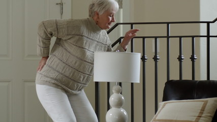 senior woman moving furniture and hurting back