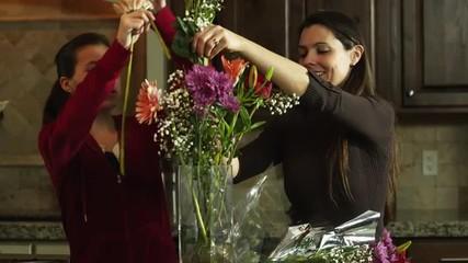 MS DS Mother and daughter (12-13) arranging flowers in vase / Orem, Utah, USA