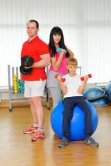 Happy family in fitness club. Happy sporty family