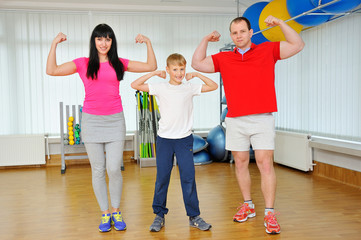 Happy family in fitness club. Happy sporty family