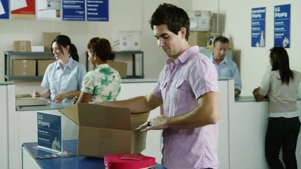 MS Man packing heart chocolate box into cardboard box at post office / Orem, Utah, USA