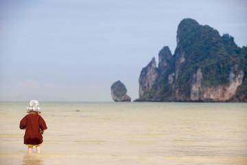 Child walking on fine sand through the water