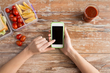 close up of hands with smartphone food on table