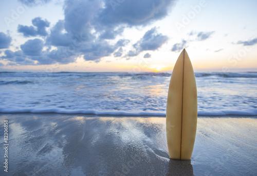 Leinwandbild Motiv Surfboard on the beach at sunset