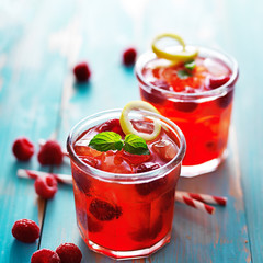 iced raspberry cocktail in two cups with mint and lemon
