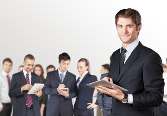 Guy. Happy smiling young businessman using his digital tablet at