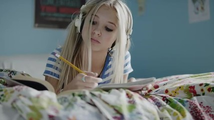 Medium shot of teenage girl doing homework and listening to music on headphones on bed / Sandy, Utah, United States