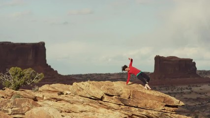 Wide shot of woman doing yoga on mountain / Moab, Utah, United States