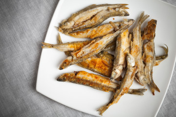 Fried smelts lays on a white plate over gray tablecloth
