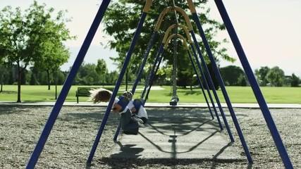 SLO MO WS PAN Boy (6-7) and girl (4-5) on swings in park / Orem, Utah, USA