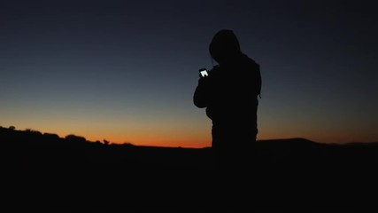 WS PAN Silhouette of person using PDA in desert at sunset/ Moab, Utah, USA