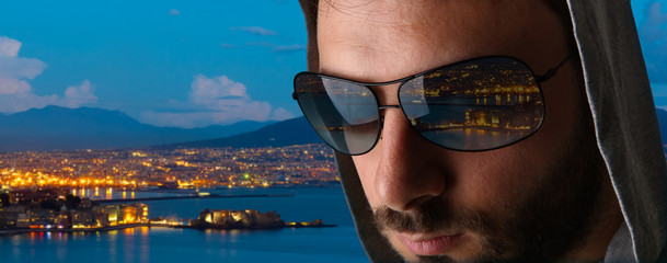 Man with the reflection of the city of Naples in the sunglasses.