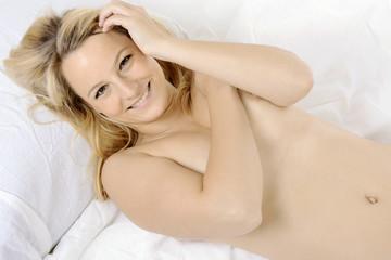 Frau liegt nackt im Bett