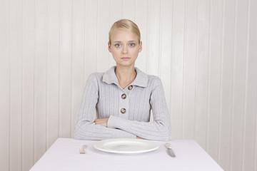 Magersüchtige Frau sitzt vor leerem Teller