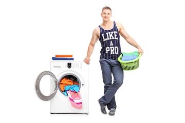 Young man posing next to a washing machine