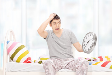 Shocked man in pajamas looking at the time in disbelief