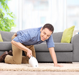 Man vacuuming with a handheld vacuum cleaner