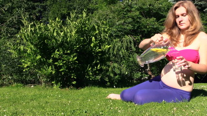 Pregnant woman drink refreshing lemon liquid in hot summer day