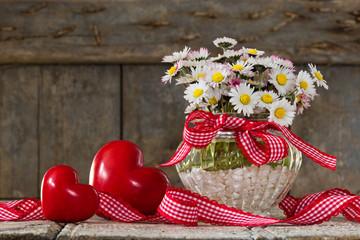 Gänseblümchen und Herzen auf Holz, Textfreiraum