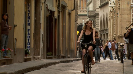 A woman riding a bike down a narrow European street