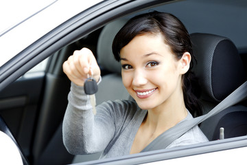 Pretty female driver in a white car showing the car key.